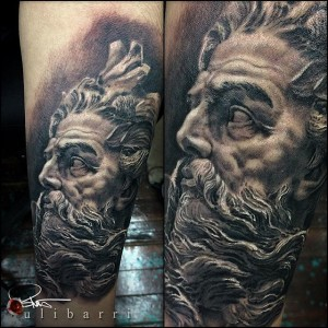 A realism black and grey portrait tattoo of Poseidon statue Tattoo by Brian Ulibarri